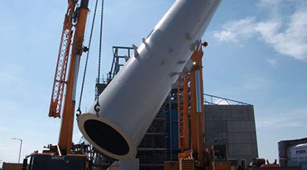 Orange crane lifting a large section of a steel chimney