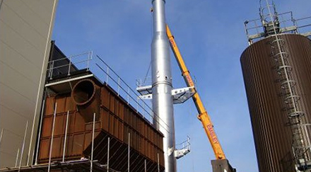 Extendable crane fixed a section of a steel chimney